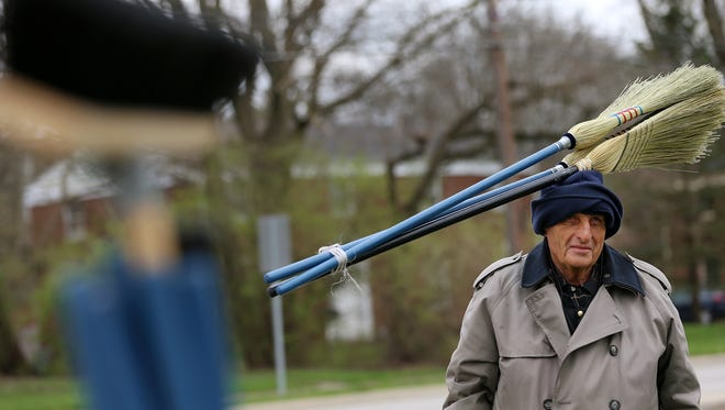 Jim Richter sells brooms Monday at the corner of 71st Street and College Avenue.