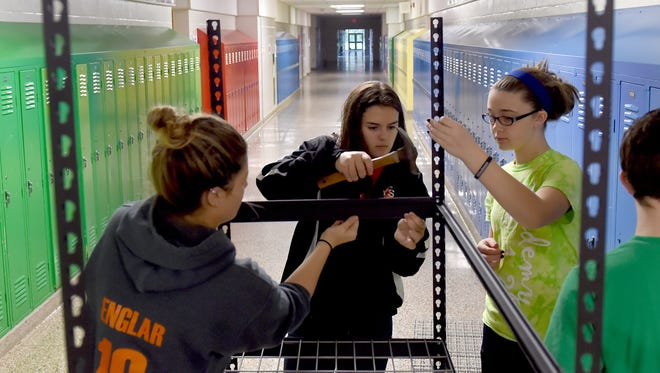 From left: Emily Englar, Sophia Guyer and Rachel Coldiron, assemble a shelving unit in the hallway at York Suburban Middle School. The students are volunteering to help build an Impact Closet at the school. The closet supplies needy students with school supplies, clothing and personal care items.