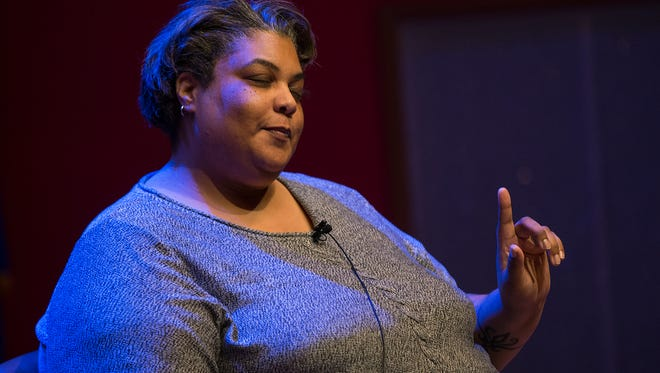 Author Roxane Gay makes the crowd laugh as she holds up a finger with attitude while answering a question from the audience at the Central Library in downtown Indianapolis, Tuesday, Jan. 24, 2017.