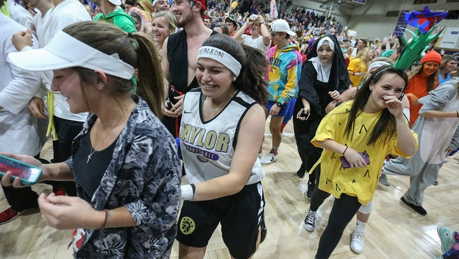 Students and fans clear the court after storming it to celebrate following the Trojans' tenth point scored during Taylor University's annual Silent Night game, Upland, Ind., Friday, Dec. 8, 2017. Students honor the decades-long tradition by dressing in costume and staying silent until the Trojans score ten points.