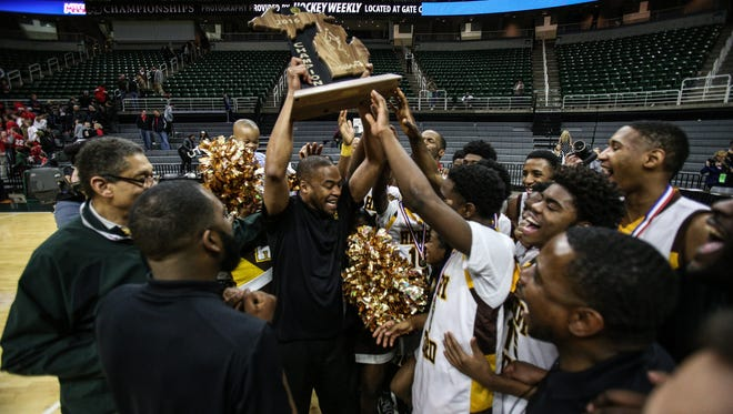 Detroit Henry Ford head coach Ken Flowers holds up the trophy after winning the MHSAA boys basketball Class B championship at the Breslin Center in East Lansing on March 26, 2016.