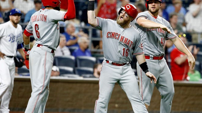 Cincinnati Reds' Billy Hamilton (6), Tucker Barnhart (16) and Scott Schebler (43) celebrate after scoring on a three-run triple by Joey Votto during the 10th inning of a baseball game against the Kansas City Royals on Tuesday, June 12, 2018, in Kansas City, Mo. The Reds won 5-1 in 10 innings (AP Photo/Charlie Riedel)