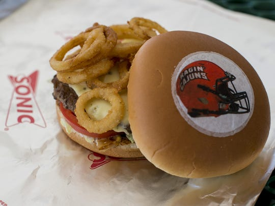 The Ragin' Cajun Burger is pictured at the Ambassador Caffery Parkway location of Sonic Drive-In in Lafayette, LA, Thursday, Sept. 3, 2015. New edible designs including a football, a helmet, and the Ragin' Cajuns logo have been placed on top of the Sonic burgers.