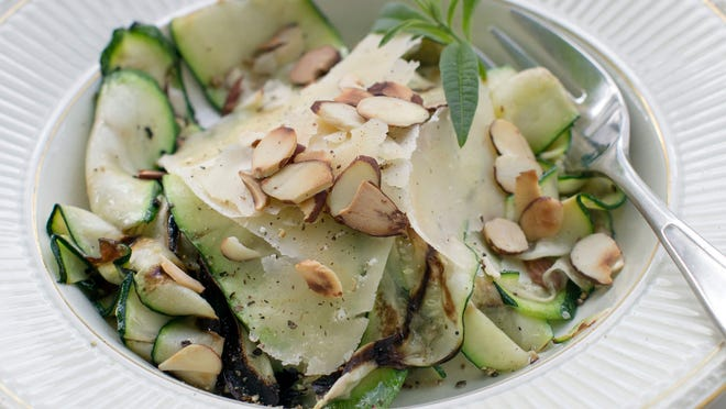 This Sept. 8, 2014 photo shows grilled zucchini ribbons with Parmesan and toasted almonds in Concord, N.H. The grilled zucchini ribbons add both flavor and visual appeal to many dishes.