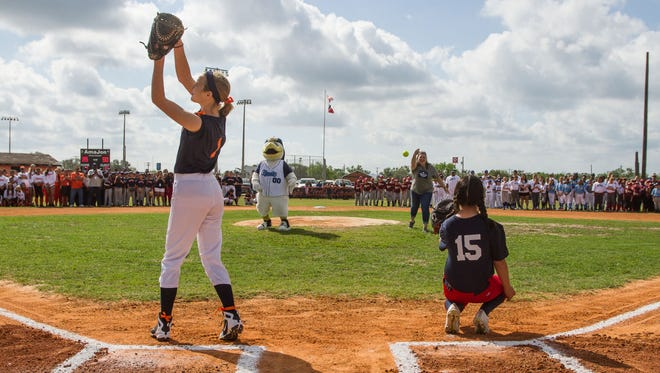 Kynslee Turner, a member of the Astros, and Emma Meza, a member of the Red Sox, participate in the ceremonial first pitch during Saturday's Refugio Little League opening ceremonies in Refugio on Saturday, March 31, 2018.