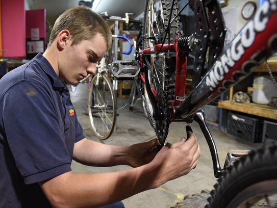 Robert Gill replaces the chain on a bicycle at the