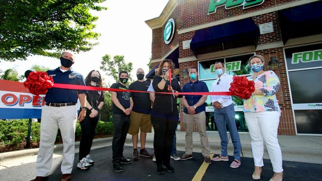 Store owner Lisa Conger prepares to cut the ribbon during a ceremony at the new PayMore to mark its grand opening Saturday morning, June 27, 2020, at its location at 2524 E. Franklin Blvd.