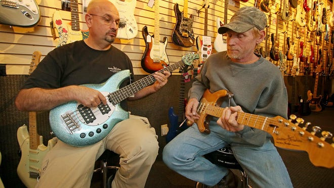 Owner Roger Calhoun plays the bass as Eric Gale plays a guitar inside Guitar Wishes on East Main Street in Lincolnton Friday afternoon, Nov. 20, 2020.