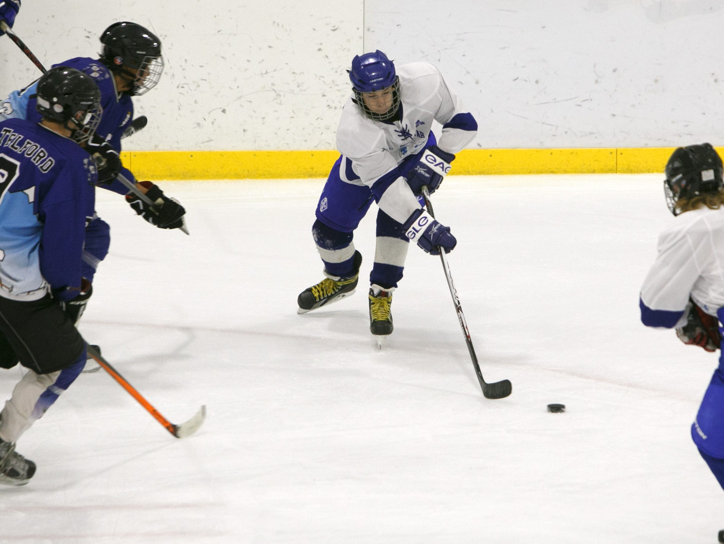 Southern Utah Independent forward Josh Moss, center, tries to get around a pair of Bingham High School players during a game at the Peaks Ice Arena in Provo, Saturday, Nov. 14, 2015.