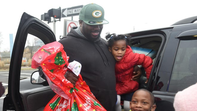 Kenyatta McCadeny holds a gift bag with his children Keymar, 6, and Kimaya, 5, after McCadeny was pulled over along Martin Luther King Boulevard on Friday during the Santa on Patrol program.