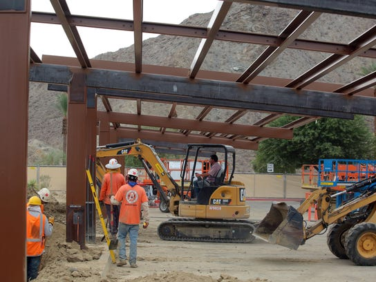 Workers build shade structures that now support solar panels in a parking lot at the east end of Rancho Mirage Public Library.