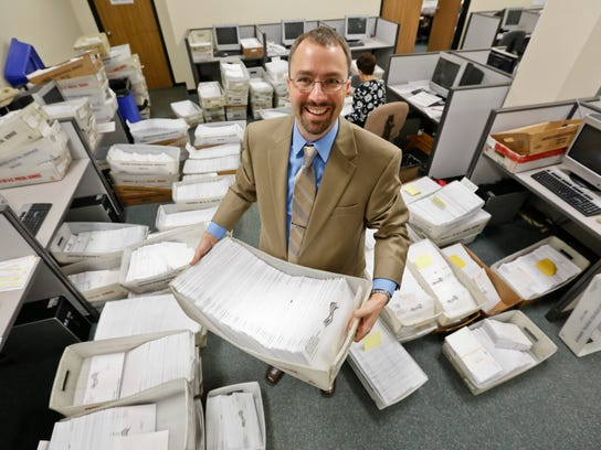 Polk County Auditor Jamie Fitzgerald is surrounding by some of the 26,000 absentee ballots that his office was handling for early voting in 2012.