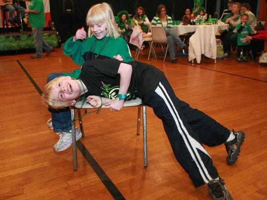 Camryn Cresci beats her brother Thomas to the last chair in a game of musical chairs at the Irish Festival at the American Turners of Delaware in Wilmington.