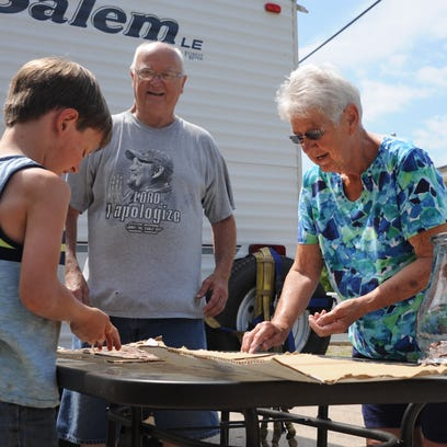 An elderly couple and a young boy wash pennies salvaged