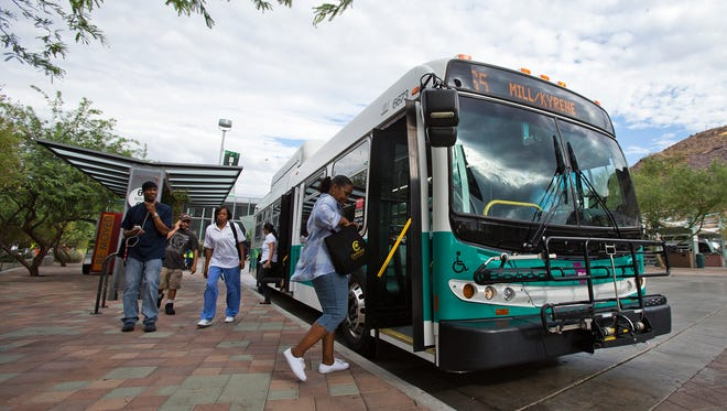 Carliss Gill, of Tempe,  boards a Valley Metro bus at the Tempe Transit Center, Friday morning, 7-19-2013.