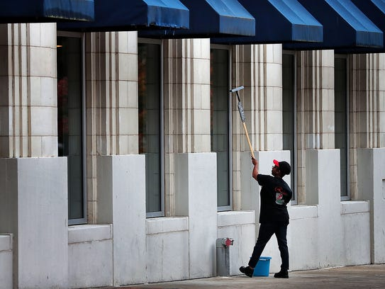Teresa Peete cleans the windows at Regina's Cajun Kitchen