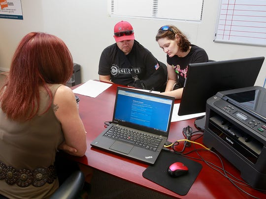 Cody and Amy Martin sign up for health insurance on Friday at the New Mexico Health Insurance Exchange office in Farmington.