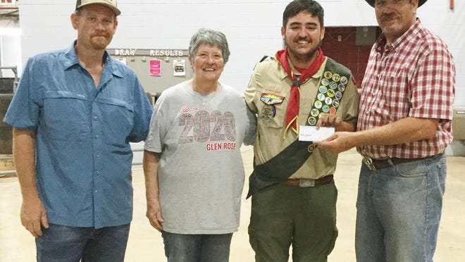 As Marc Moss receives his scholarship check from Somervell County Rodeo on Aug. 12, he is wearing his Boy Scouts uniform because he had just attended his Eagle Scout Ceremony. Pictured (from left) are Marc's father Jeremiah Moss, Brenda Ransom, Marc Moss and Gerry Byrn.