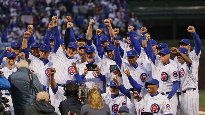 Members of the Chicago Cubs show off their World Series championship rings before a game against the Los Angeles Dodgers at Wrigley Field.