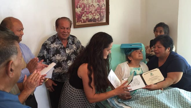 Genoveva Manglona, 89, wearing graduation cap, receives her honorary diploma Monday July 10, 2017, from Southern High School during a ceremony at her Inarajan home.