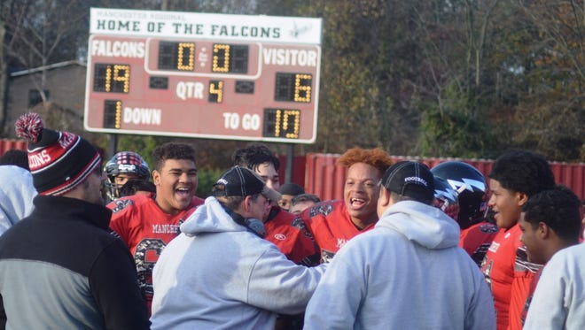 Manchester coach Rande Roca (center) celebrating with his team after a 19-6 victory in the North 1, Group 2 playoffs.