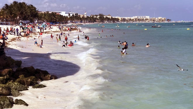 Tourists enjoy the beach at the Playa del Carmen.