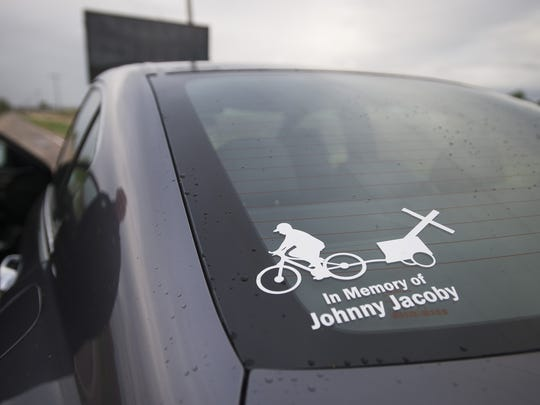 A sticker memorializes John Jacoby on the back of his brother, David's, car. John Jacoby was murdered while riding his bicycle along the same road in May 2015.