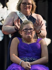"Jennifer Cobb, the 2016 Miss Golden, places a crown on Ali Shanks as she is awarded ""Biggest Heart,"" during the 2017 Miss Golden pageant. The 12-year-old's hobbies include baking, cheer, baseball, swimming and playing with slime and fidget spinners."