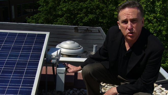 John Byrne, director of the Center for Energy and Environmental Policy at the University of Delaware, shows off solar panels on the roof of the center at Graham Hall on the UD campus.