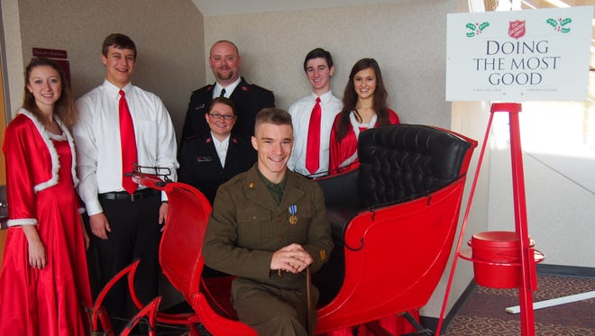 """Fond du Lac High School actors hope to fill the sleigh with food donations by the time the """"White Christmas"""" is over. Standing, from left, are students Nicole Thiel and Loren Kelly, Salvation Army Captains Telinda and Steve Wilson, and students Jack Caufield and Maya Mockert. Seated in the sleigh is Paul Millard."""