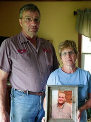 Bob and Diane Biadasz, parents of the late Michael, hold a portrait of their son in their home Aug. 19, 2016. Michael died from manure fumes while working on the family farm earlier that week.
