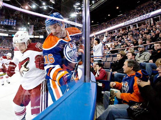Arizona Coyotes' Brandon McMillan (22) checks Edmonton Oilers' Teddy Purcell (16) during the first period of an NHL hockey game in Edmonton, Alberta., on Monday, Dec. 1, 2014.  (AP Photo/The Canadian Press, Jason Franson)