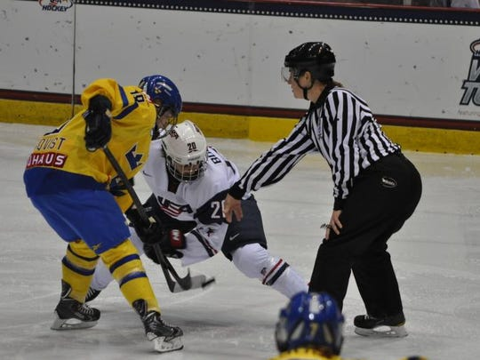 Laura Johnson, of Rochester, drops the puck during a women's hockey game between Sweden and the United States. Johnson has been chosen to work at the 2014 Winter Olympics in Russia.