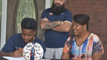 Richmond Hill's Cam Brown signs a letter of intent to play soccer for Brewton-Parker College in Mount Vernon. His mother, Wendelyn Brown, and Brewton-Parker soccer coach Frankie Ruiz attended the ceremony.
