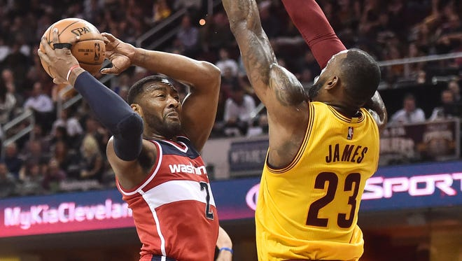 Washington Wizards guard John Wall (2) drives to the basket against Cleveland Cavaliers forward LeBron James (23) during the first half at Quicken Loans Arena.
