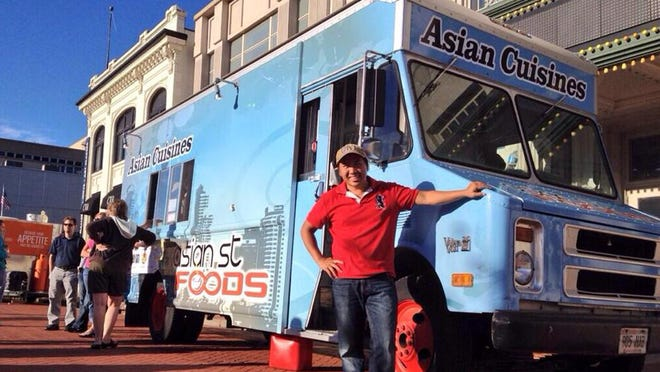 T'xer Zhon Kha, owner of Asian St. Cuisine and Daily Herald Media photographer, stands in front of his food truck. He opened the mobile restaurant in 2013.