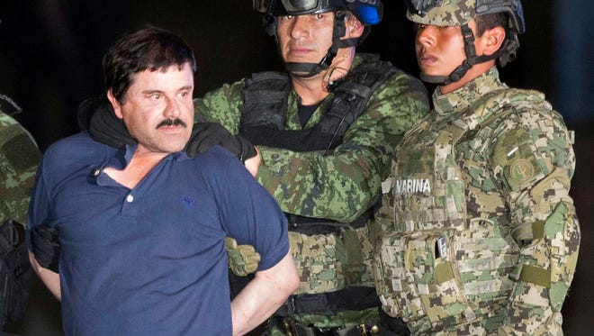 "Joaquin ""El Chapo"" Guzman faces the press as he is escorted to a helicopter in handcuffs by Mexican soldiers and marines at a federal hangar in Mexico City, Mexico, on Jan. 8, 2016."