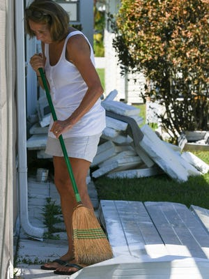 Jand Beaudette sweeps up around her father's home in Barefoot Bay. The carport was torn off during Hurricane Irma. Mandatory Credit: Craig Bailey/FLORIDA TODAY via USA TODAY NETWORK