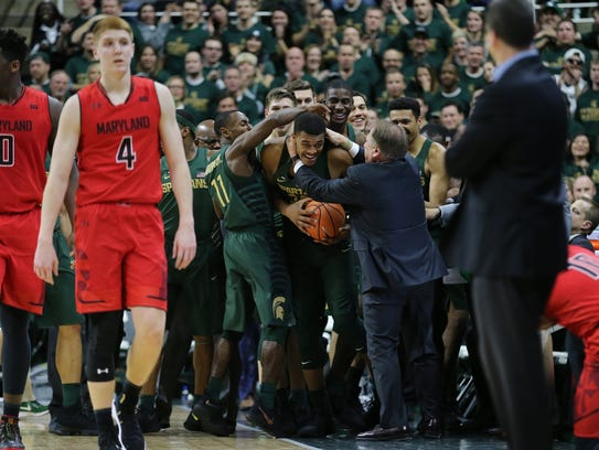 MSU coach Tom Izzo celebrates with Xavier Tillman, center, in the first half against Maryland on Thursday.