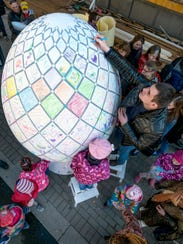 Orthodox believers paint a giant Easter egg during