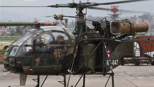 """A Nepalese army chopper, that spotted the suspected wreckage of a U.S. Marine helicopter, lands at the airport in Kathmandu, Nepal, Friday, May 15, 2015. Nepalese rescuers on Friday found three bodies near the wreckage of the chopper that was carrying six Marines and two Nepalese army soldiers. The U.S. Marines said they were sending their own rescue team to assess the wreckage and determine if it was the missing helicopter, the UH-1 """"Huey."""" (AP Photo/Bernat Armangue)"""