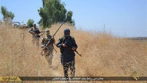 """In this photo released on June 23, 2015, by a website of Islamic State militants, Islamic State militants patrol Khazer, Iraq, near Mosul. The group's conventional and guerrilla tactics carried it to an overwhelming sweep of northern and western Iraq in 2014, capturing Mosul, Iraq's second-biggest city. Shortly thereafter, IS leader Abu Bakr al-Baghdadi declared a """"caliphate"""" spanning its territory in Iraq and Syria. (Militant website via AP)"""