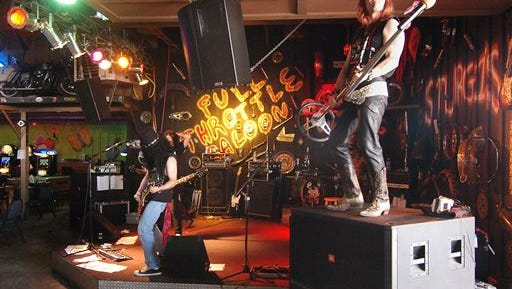 """FILE - In this Aug. 7, 2006 file photo, a Guns and Roses tribute band plays at the Full Throttle Saloon in Sturgis, S.D., during the Sturgis Motorcycle Rally. An early morning fire Tuesday, Sept. 8, 2015, destroyed the popular saloon that billed itself as the """"world's largest biker bar."""" The bar, which featured such amenities as zip lines, musical stages and rental cabins, had been the subject of a reality television series. The cause of the fire remains under investigation. (AP Photo/Doug Dreyer, File)"""