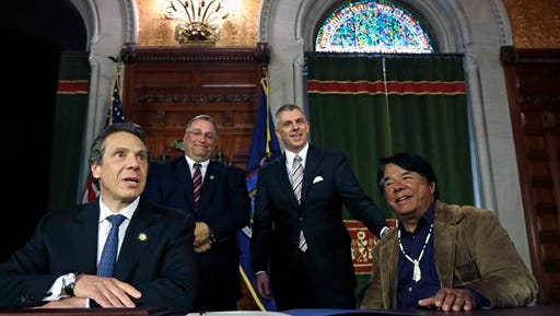 From left, New York Gov. Andrew Cuomo, Madison County Board of Supervisors' John Becker, Oneida County Executive Anthony Picente and Ray Halbritter of the Oneida Indian Nation pose after a news conference on Thursday, May 16, 2013, in Albany, N.Y. The Oneidas have struck a deal with the Cuomo administration to guarantee exclusive territory for their central New York casino in exchange for an estimated $50 million in annual payments to the state. The proposed deal would be part of Cuomo's proposal to bring three Las Vegas casinos to upstate New York at yet-to-be-identified locations. (AP Photo/Mike Groll)