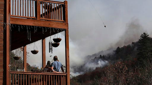 Eric and Vebbra Willey look on from the porch of their home as a helicopter works on dropping water on the approaching Rock Mountain wildfire, Wednesday, Nov. 16, 2016, in Tate City, Ga. Residents are under a pre-evacuation order as firefighters work to keep the fire away from their homes. (Curtis Compton/Atlanta Journal-Constitution via AP)