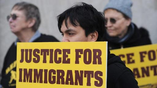 """Chris Magno, of Erie, holds a pro-immigration sign Wednesday, Feb. 22, 2017 during a """"Build Bridges Not Walls'' immigration vigil at Perry Square in Erie, Pa. near the U.S. District Courthouse. Magno, an assistant professor of criminal justice at Gannon University in Erie, is an immigrant from the Philippines who has permanent residency, or """"green card"""" status. About 60 attended the vigil, where speakers denounced President Donald Trump's temporary immigration and refugee bans."""