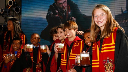 FILE - In this Dec. 6, 2011. file photo, fans dress up as students from Hogwarts School of Witchcraft and Wizardry make a butterbeer toast as Universal Parks & Resorts announces the Harry Potter attraction is coming to Universal Studios Hollywood in Universal City, Calif. Pennsylvania's Yuengling's Ice Cream launched a butterbeer flavored ice cream on March 20, 2017.