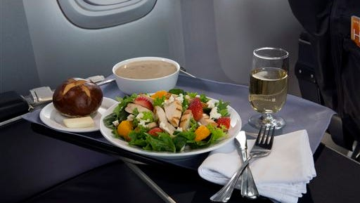 This product image provided by United Airlines shows a Strawberry Fields Salad, one of a variety of the airline's new first class food options.  The Chicago-based airline on Thursday announced that it?s upgrading first class food options and replacing snacks with full meals on some of its shortest flights.