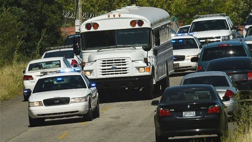 Police officers escort UPS employees on a bus from the scene where three people were killed, including the gunman, at a UPS facility in Birmingham, Ala., today.