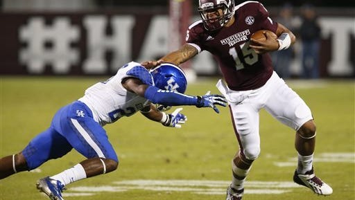 Mississippi State quarterback Dak Prescott (15) fights off a tackle attempt by Kentucky safety Eric Dixon (28) as he runs for long yards in the first half of their NCAA college football game at Davis Wade Stadium in Starkville, Miss., Thursday, Oct. 24, 2013.